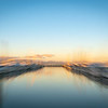 Abstract impressionist style Tauranga Marina boats and piers reflected in calm water at sunrise