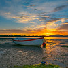 Backlighting of small boat at low tide on beach by sunrise across harbour and behind distant hills.
