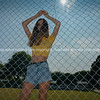 Teenage girl with arms up behind net fence..