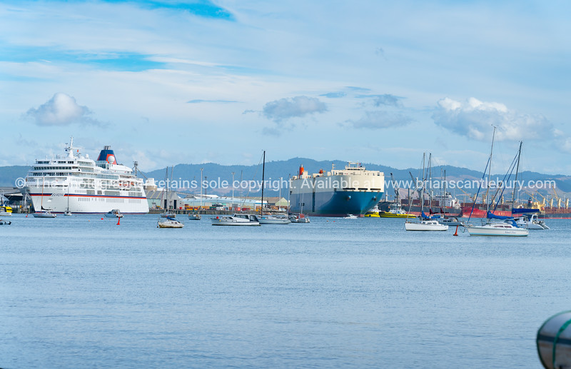 Cruise ship moored at wharf and cargo ship leaving with moored yachts
