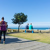 Eldery couple rest and look at scenic ocean view on becnh seat along Mount Maunganui ocean-beach with people passing on boardwalk.