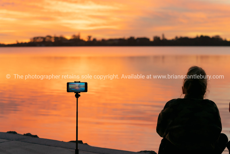 Brilliant sunrise being recorded on mobile device with silhouette of woman sitting by water's edge.