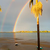 Rainbow falls to horizon then reflects across bay to dinghy sitting on beach