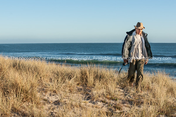 Tourist with camera walks along sand dunes at Papamoa.