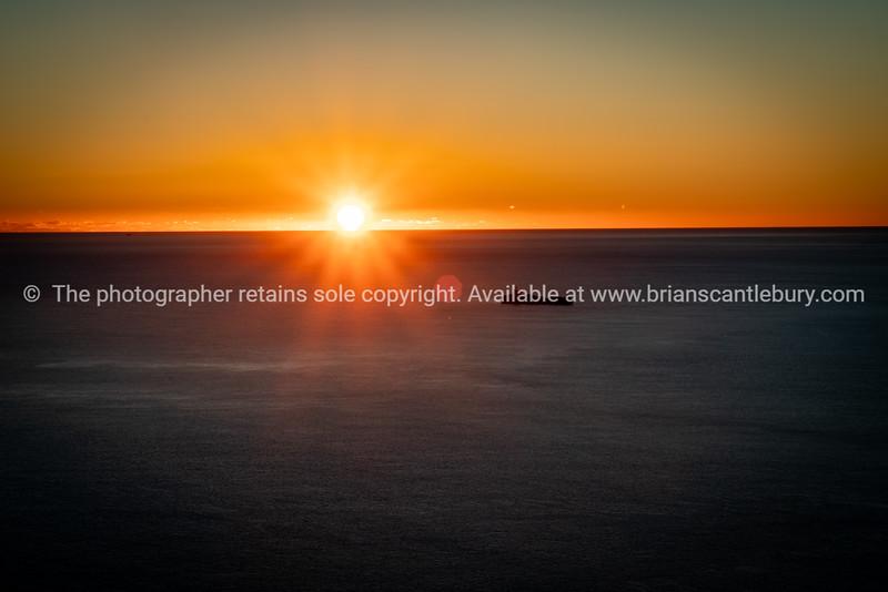 Ocean sunrise and lower slopes of Mount Maunganui
