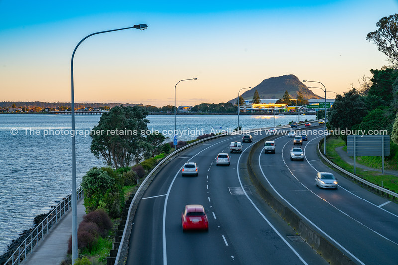 Cars in long exposure  blurred in motion travelling along Takitimu Drive with landmak Mount Maunganui in distance at sunrise.
