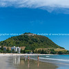 People enjoying summer day on Mount Maunganui Main Beach with Mount in background.