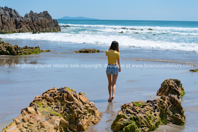 Young woman in bright yellow top walking near waters edge