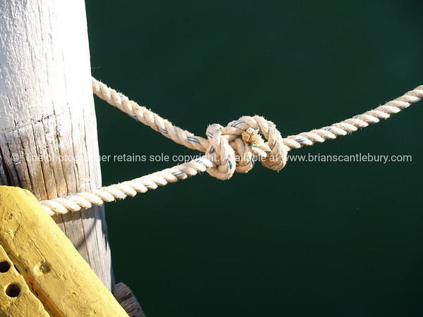 """Knot at dock . Tauranga scenics.<br /> Tied off. Mooring rope and knot close up. Tauranga is New Zealands 5th largest city and offers a wonderfull variety of scenic and cultural experiences. Tauranga stock images Tauranga scenics. See;  <a href=""""http://www.blurb.com/b/3811392-tauranga"""">http://www.blurb.com/b/3811392-tauranga</a> mount maunganui landscape photography, Tauranga Photos; Tauranga photos, Photos of Tauranga Also see; <a href=""""http://www.brianscantlebury.com/Events"""">http://www.brianscantlebury.com/Events</a>"""