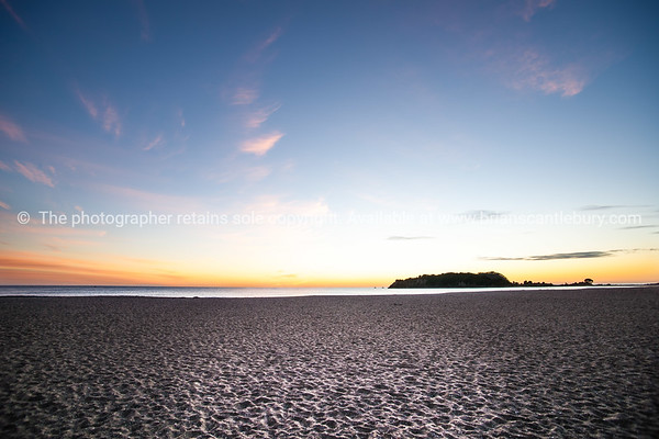 Mount Maunganui's Leisure island (Moturiki Island) floats on the horizon just before sunrise.