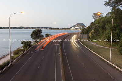 Highway red and yellow lightstreams along Takitimu Drive at dusk looking north with Mount Maunganui on horizon.