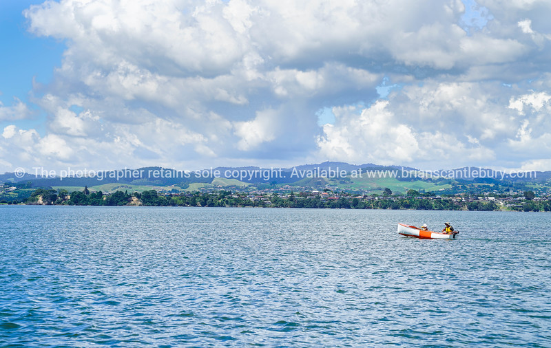 Man and child motoring in small orange and white dinghy.