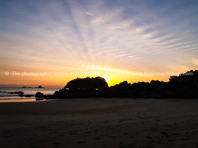 Sunsets over the base of Mount Maunganui.