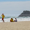 Two young lifeguards and a boy sit on hazy beach watch the rough dangerous surf.