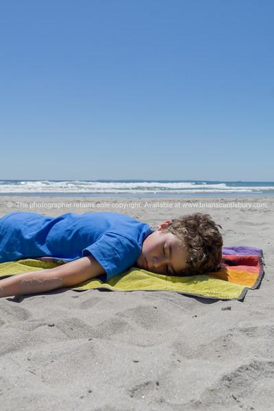 Boy lying on towel on beach