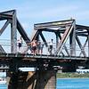 Jumping from historic steel truss Tauranga Railway bridge in harbour below.
