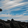 Wispy clouds blow across the sky over Mount Maunganui's rocky base.