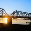 Railway bridge silhouetted by sunrise