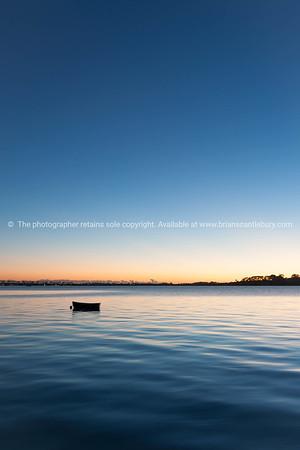 Sunrise across bay with small dinghy blue tones with orange around horizon