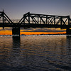 Silhouette steel truss bridge structure against glow fo sunrise on horizon,