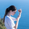 Teenager on top Mount Maunganui checking device while shading screen