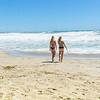 Young women at beach entering water enjoying summer day outdoors.