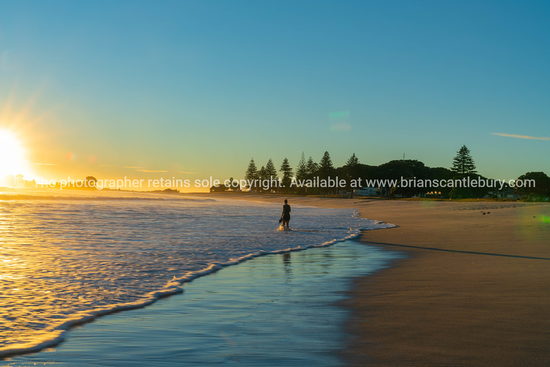 Small unrecognizable figure of woman walking away on beach