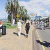 People walking on footpath past recycling bins.