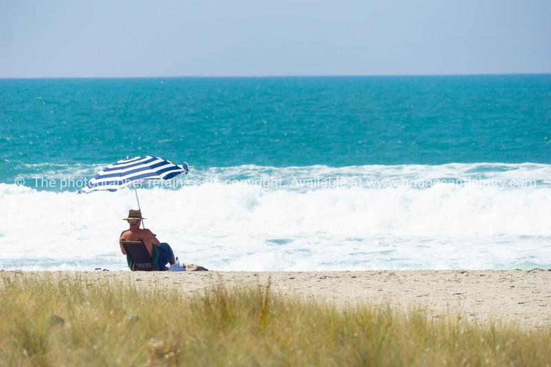 Lone man on beach under striped umbrella