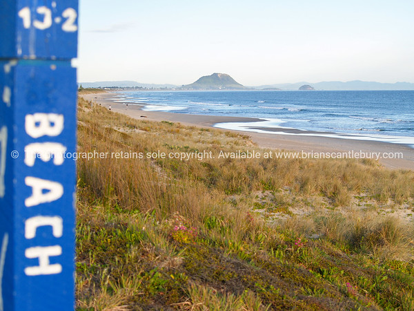 Long Papamoa beach view to Mount Maunganui from Beach access sign