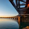 Sunrise across Tauranga harbour catches historic railway bridge.