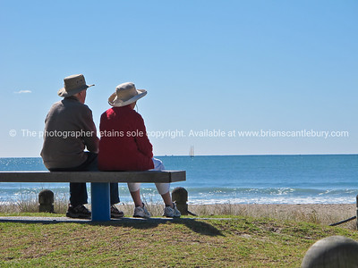Elderly couple sit on seat at base of the Mount looking out to the ocean