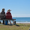 Elderly couple sit on seat at base of the Mount looking out to the ocean Tauranga, Mount Maunganui photos