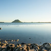 """Dingy on calm water, Mount Maunganui and Matakana Island on horizon beyond. - 4 See;  <a href=""""http://www.blurb.com/b/3811392-tauranga"""">http://www.blurb.com/b/3811392-tauranga</a> mount maunganui landscape photography, Tauranga Photos; Tauranga photos, Photos of Tauranga Also see; <a href=""""http://www.brianscantlebury.com/Events"""">http://www.brianscantlebury.com/Events</a>"""