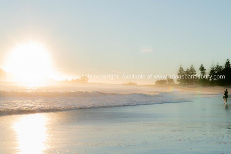 sunrise on beach as waves roll in