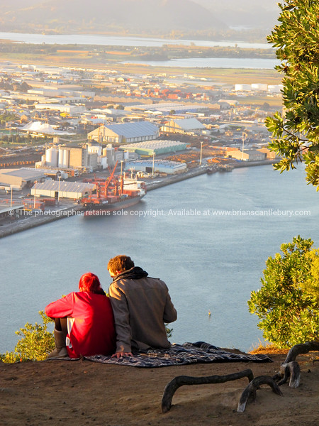 """Young couple share early morning light from top of Mount maunganui with the port and industrial area in background. Tauranga is New Zealands 5th largest city and offers a wonderfull variety of scenic and cultural experiences. Tauranga stock images Tauranga scenics.<br /> Model Release; no. See;  <a href=""""http://www.blurb.com/b/3811392-tauranga"""">http://www.blurb.com/b/3811392-tauranga</a> mount maunganui landscape photography, Tauranga Photos; Tauranga photos, Photos of Tauranga Also see; <a href=""""http://www.brianscantlebury.com/Events"""">http://www.brianscantlebury.com/Events</a>"""