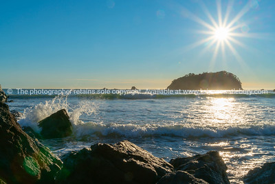 Lens flare, stunning over rocky coastal edge