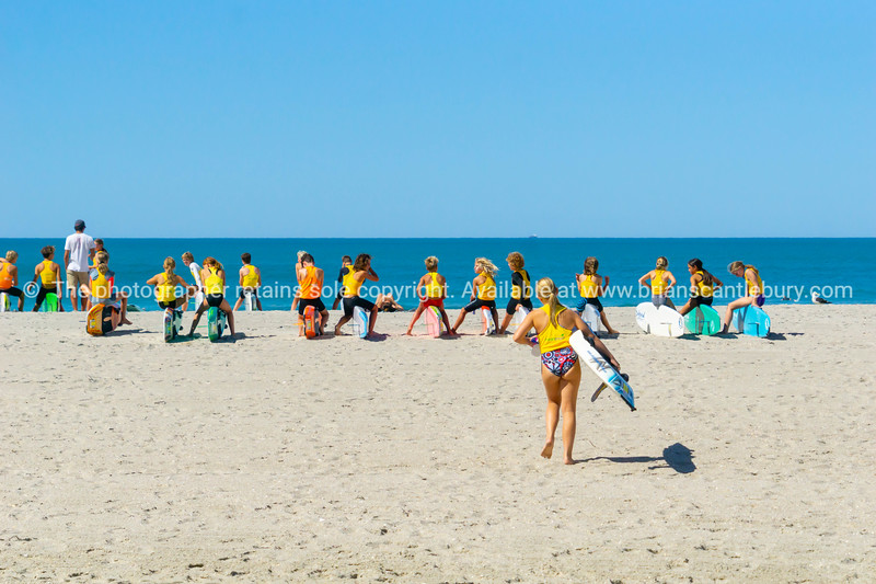 Girl carrying board walks toward group young club members lined up and waiting on beach
