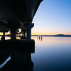 Curving lines and calm water by Tauranga Harbour Bridge and colour in the sky at sunrise