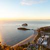 Mount Maunganui township below as sun rises on horizon and falls across ocean beach and buildings below