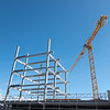 heavy steel frame rising into blue sky as new building ic constructed