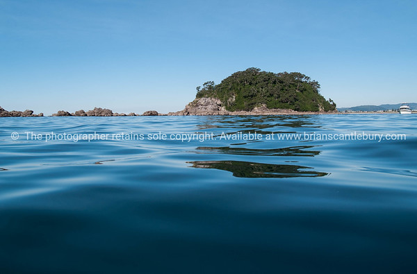 Off-shore island across blue of ocean from low point of view with Mount Maunganui beach bachground.