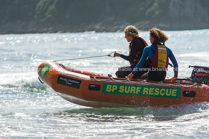Mount surf Life Savers heading out through waves on inflatable.