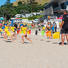 Children learning basics of fitness with Mount Maunganui Surf Life Saving Club on Main Beach on hot summer day