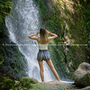 Young modern woman sitting on rock looking at McLaren Falls waterfall, Tauranga New Zealand. Model Released; Yes.