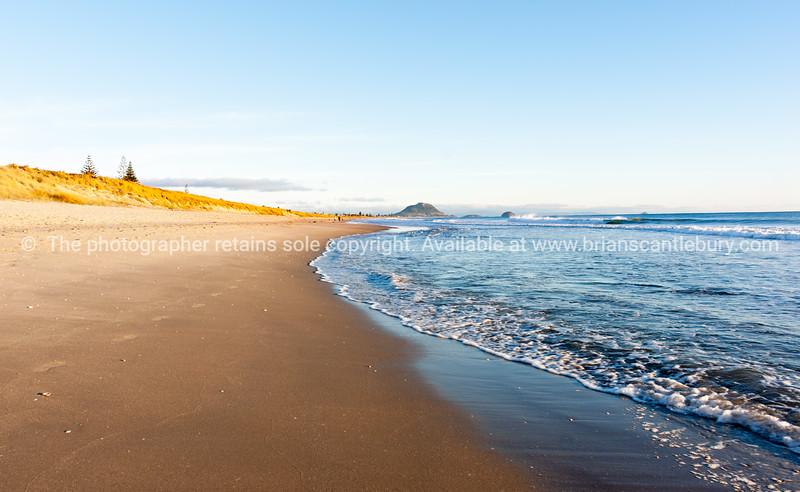 Golden morning on Papamoa Beach with Mount Maunganui on distant horizon