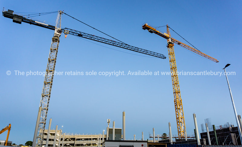 Two tall construction cranes on city redevelopment site for the new Farmers building.