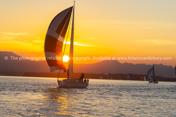 Yachts under sail and silhouette of setting sun