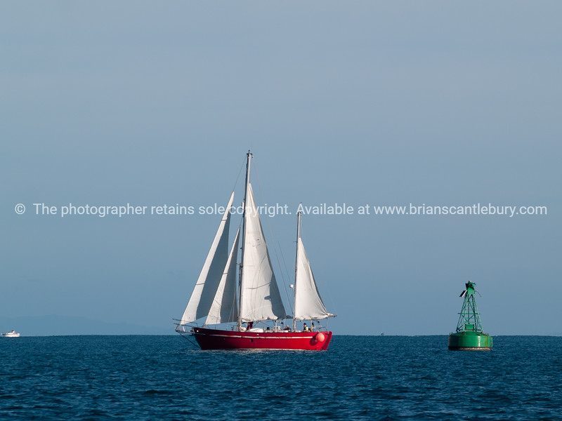 Classic style yacht with red hull siails past