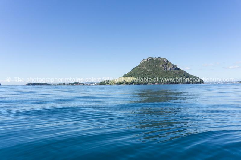 landmark Mount Maunganui over calm blue sea on horizon.